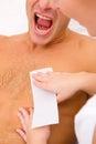 Man yelling while waxing torso on spa saloon Royalty Free Stock Photo
