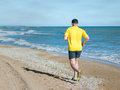 The man in the yellow shirt performs a morning jog on the beach. Royalty Free Stock Photo