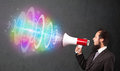 Man yells into a loudspeaker and colorful energy beam comes out handsome guy Royalty Free Stock Photography