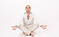 Man in yoga position dressed white sitting relaxing and doing Stock Photography