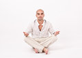 Man in yoga position dressed white sitting relaxing and doing Royalty Free Stock Image