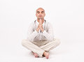Man in yoga position dressed white sitting relaxing and doing Stock Photos