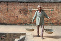Man with yoke bhaktapur nepal circa november walk near the brick wall Stock Photo