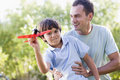 Man and young boy outdoors playing with toy plane Royalty Free Stock Images