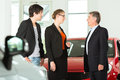 Man with young couple in car dealership Stock Images