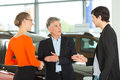 Man with young couple in car dealership Royalty Free Stock Photo