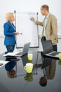 Management team at flip over board side view of two managers discussing a diagram on aflipchart in conference room Royalty Free Stock Images