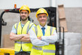 Manager with arms crossed and his colleague behind him in warehouse Stock Photo