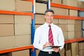 Manager with clipboard in distribution warehouse happy writing on Royalty Free Stock Images