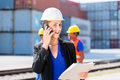 Manager with phone talking on shipment yard in front of container Stock Photo