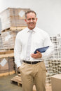 Manager standing with hand in the pocket holding tablet pc a large warehouse Royalty Free Stock Images