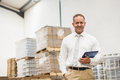 Manager standing with hand in the pocket holding tablet pc a large warehouse Stock Photo