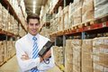 Manager in warehouse smiling with bar code scanner Royalty Free Stock Photography
