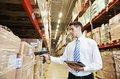 Manager in warehouse worker with bar code scanner Royalty Free Stock Images