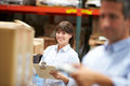 Manager in warehouse with worker scanning box in foreground smiling to camera Royalty Free Stock Photography