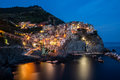 Manarola a picturesque coastal village with colorful old houses illuminated at dusk in italy Stock Photos