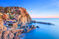 Manarola village, rocks and sea at sunset. Cinque Terre, Italy Royalty Free Stock Photo