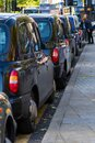 A row of black cabs waiting for customers Royalty Free Stock Photo