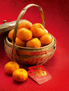 Mandarins in a basket and red packets in red clot Stock Photos