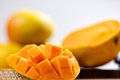 Mango cubes slices close up macro with mangos in background Royalty Free Stock Photos