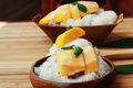 Mango sticky rice is put in a wooden container placed on a brown Royalty Free Stock Photo