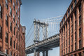 Manhattan bridge seen from narrow buildings on a sunny day Royalty Free Stock Photo