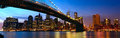 Manhattan panorama lower skyline with brooklyn bridge at sunset in new york city Stock Images