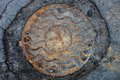 Manhole with rusty metal cover in cracked asphalt surface Royalty Free Stock Photo