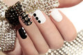 Manicure on short nails covered with black and white lacquered with rhinestones a black background Royalty Free Stock Photography
