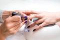 Manicurist applies nail gel polish middle finger