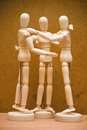 Manikin group hug of three art manikins in a huddle Stock Image