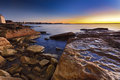 Manly rocks rise australia nsw beach in sydney sunrise over sandstone coastline surfing waves and distant shore Royalty Free Stock Photography