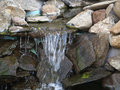 Manmade rock waterfall fountain pond outdoors moss outdoor rocks landscaping Royalty Free Stock Photography
