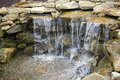 Manmade waterfall pours over pebbles rust colored sandstone forms a that splashes rocks and in a wealthy backyard Stock Photos