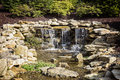 Manmade waterfall water feature a pours out over constructed sandstone into babbling brook with overhangs of thin shrubbery Stock Photography