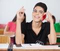Mannelijke student looking away while die op telefoon spreken Stock Foto