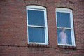 Mannequin in window a female standing looking out of a second story an old building Stock Photos