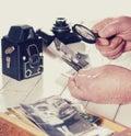 Manos del viejo hombre fotos con la lupa a partir del pasado cámaras retras de la visión en la tabla filtrada Imagen de archivo libre de regalías