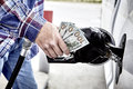Mans Hand holding Cash while Refueling Vehicle Royalty Free Stock Photo