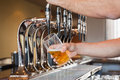 Mans hand pouring beer pint of behind the bar Stock Image