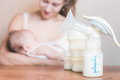 Manual breast pump and mother feeding a newborn baby Royalty Free Stock Photo