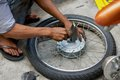 Manual motorbike wheel repair on street in vietnam Royalty Free Stock Images
