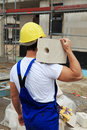 Manual worker carrying brick Royalty Free Stock Image