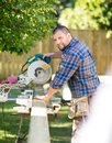 Manual worker cutting wood using table saw at site portrait of happy mid adult construction Stock Image