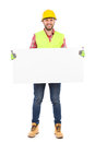 Manual worker posing with white placard construction in yellow helmet and reflective waistcoat holding full length studio shot Stock Images