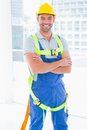 Manual worker wearing safety harness in bright office portrait of happy standing arms crossed Stock Image
