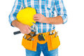 Manual worker wearing tool belt while holding hammer and helmet Royalty Free Stock Photo