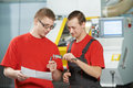 Manufacture technician workers discussing and measure detail near cnc milling machine center at tool workshop Stock Image