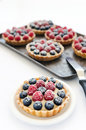 Many appetising fruit tarts yummy looking mix berry with shallow depth of field Stock Photo