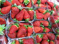 Many baskets plastic red strawberries sale market Stock Photo